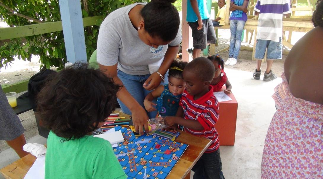 A volunteer with children in Belize helps two young students with an educational activity at a kindergarten.